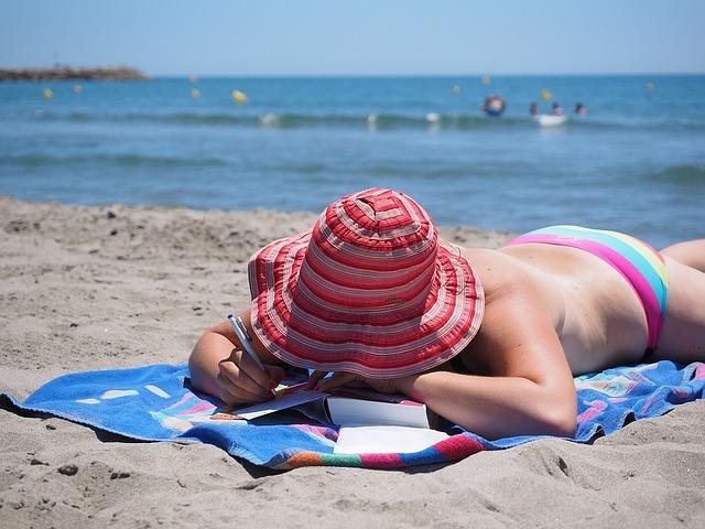 žena na pláži píšící pohlednici