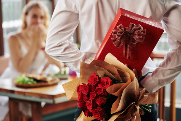 man-hiding-bouquet-roses-giftbox-his-back-as-birthday-present-girlfriend_274689-16872